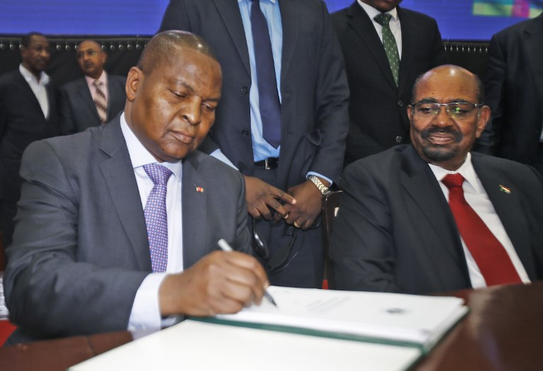 Central African president Faustin-Archange Touadera (L) inks a peace deal next to Sudanese President Omar al-Bashir in Khartoum on February 05, 2019. ASHRAF SHAZLY / AFP