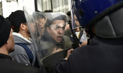 An angry protester faces security agents in Algiers