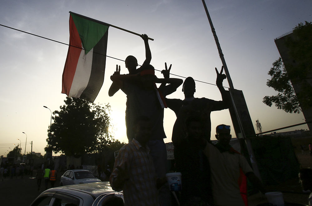 Sudanese protesters wave the national flag