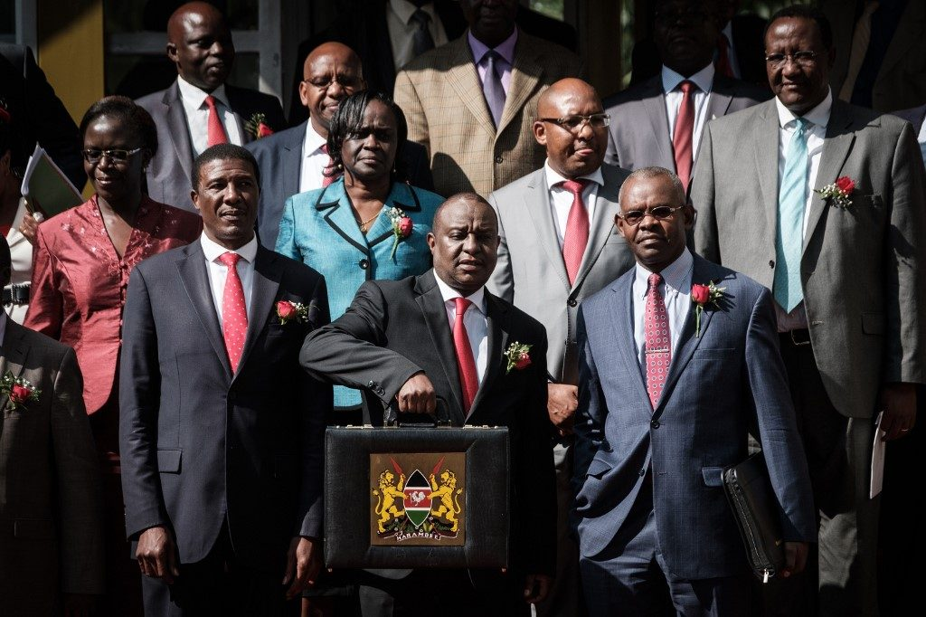 Kenya's Cabinet Secretary for National Treasury Henry Rotich (C) poses with the budget briefcase before leaving for Parliament
