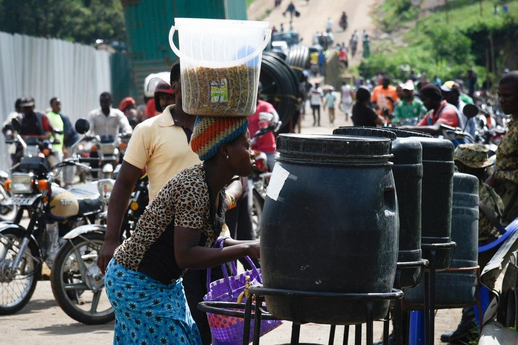 Democratic Republic of Congo (DRC) wash their hands at the Ebola screening point