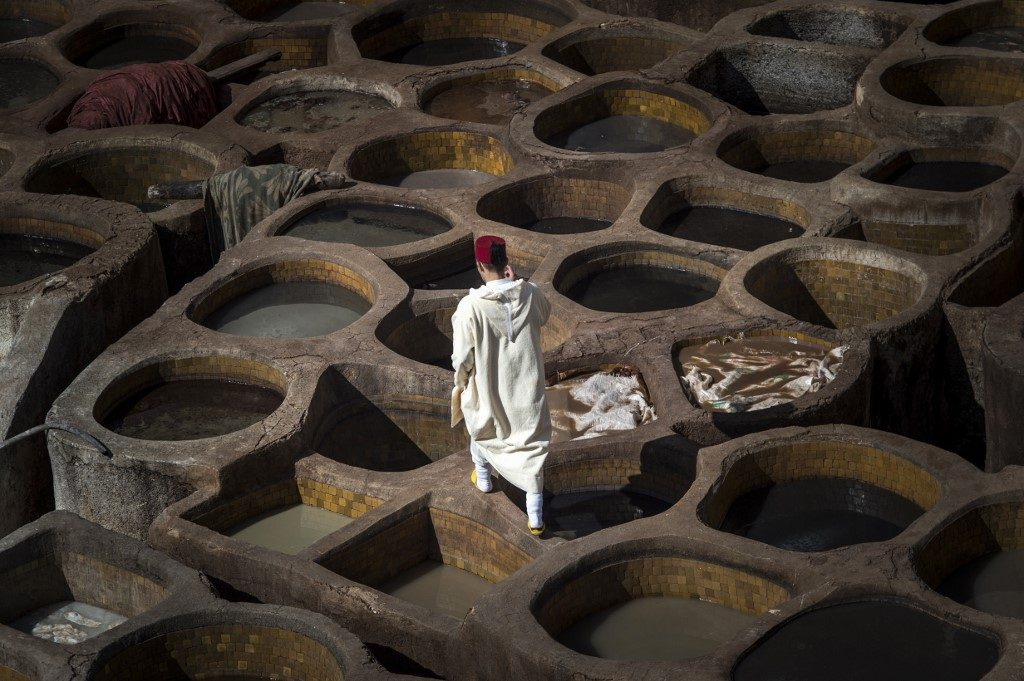A Moroccan man walks in the tannery in the 9th century walled medina in the ancient city of Fez