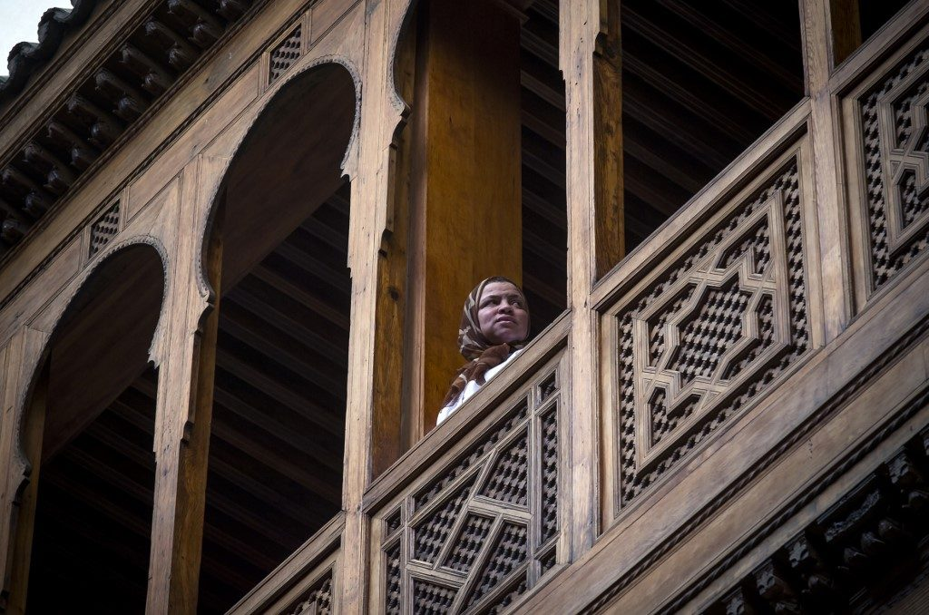 A woman stands in the balcony of a traditional building in the 9th century walled medina in the ancient Moroccan city of Fez