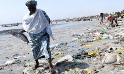 A woman holding a fish walks on tyre and plastic waste on June 1, 2019 in Dakar's highly populated Hann Bay