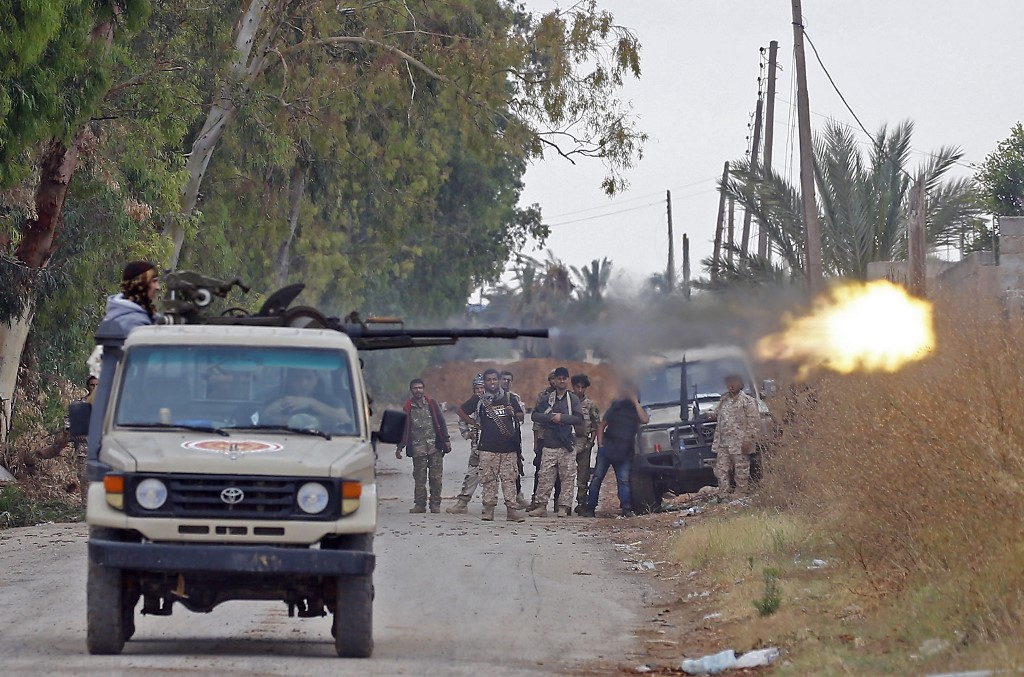 A fighter loyal to the Libyan internationally-recognised Government of National Accord (GNA) fires a heavy machine gun