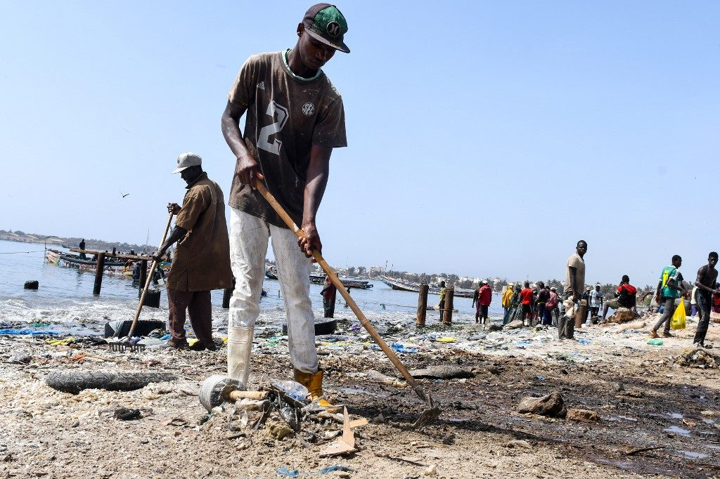 A volunteer cleans up a beach littered with tyre, plastic waste and dead fishes on June 1, 2019 in Dakar's highly populated Hann Bay