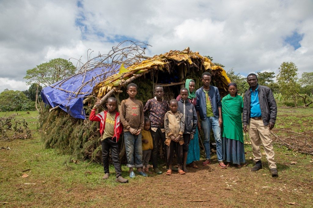 A group of people displaced due to the ethnic tensions in Ethiopia pose in front of their shelter on May 20, 2019 at Qercha village, southern Ethiopia