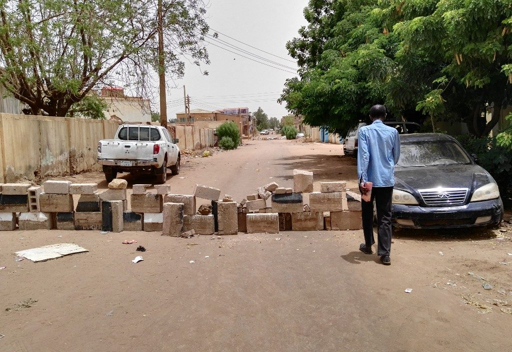 A Sudanese man walks towards a barricade made of bricks to block a street for cars in Khartoum's twin city Omdurman on the first day of a civil disobedience campaign