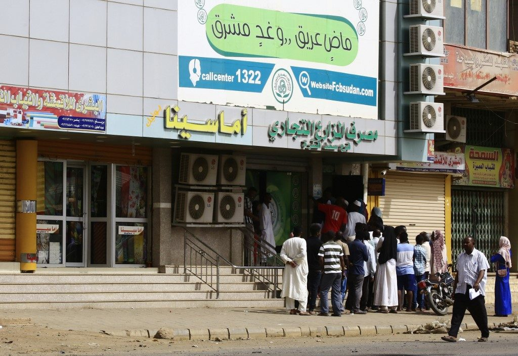 Residents of Khartoum queue outside a bank to withdraw money in the Sudanese capital