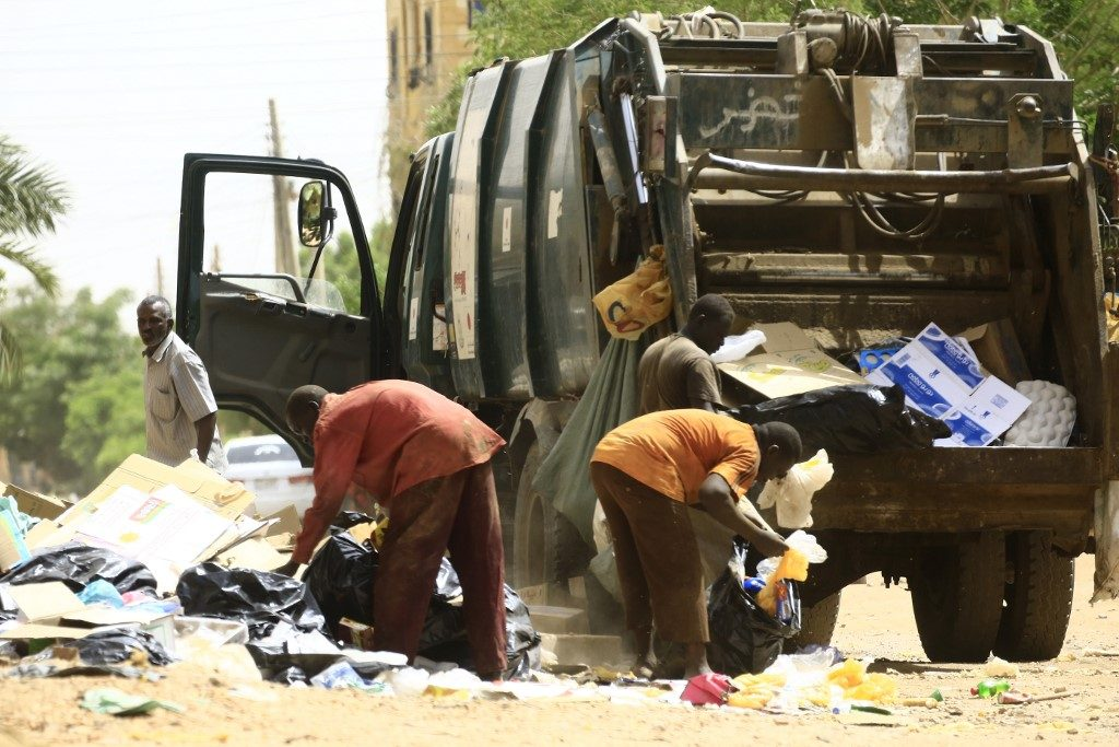 Municipality workers clean up the streets in the Sudanese capital Khartoum on June 12, 2019.