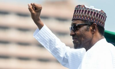 Nigerian President Muhammadu Buhari who quoted Mandela, raises his fist during an inspection of honour guards on parade to mark Democracy Day in Abuja