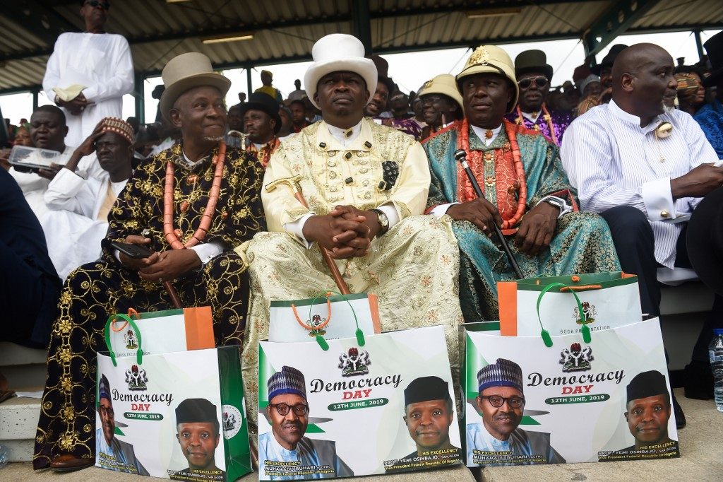 People wearing traditional costumes display gift bags with the pictures of the Nigerian President Muhammadu Buhari and Vice President Yemi Osinbajo during the Democracy Day