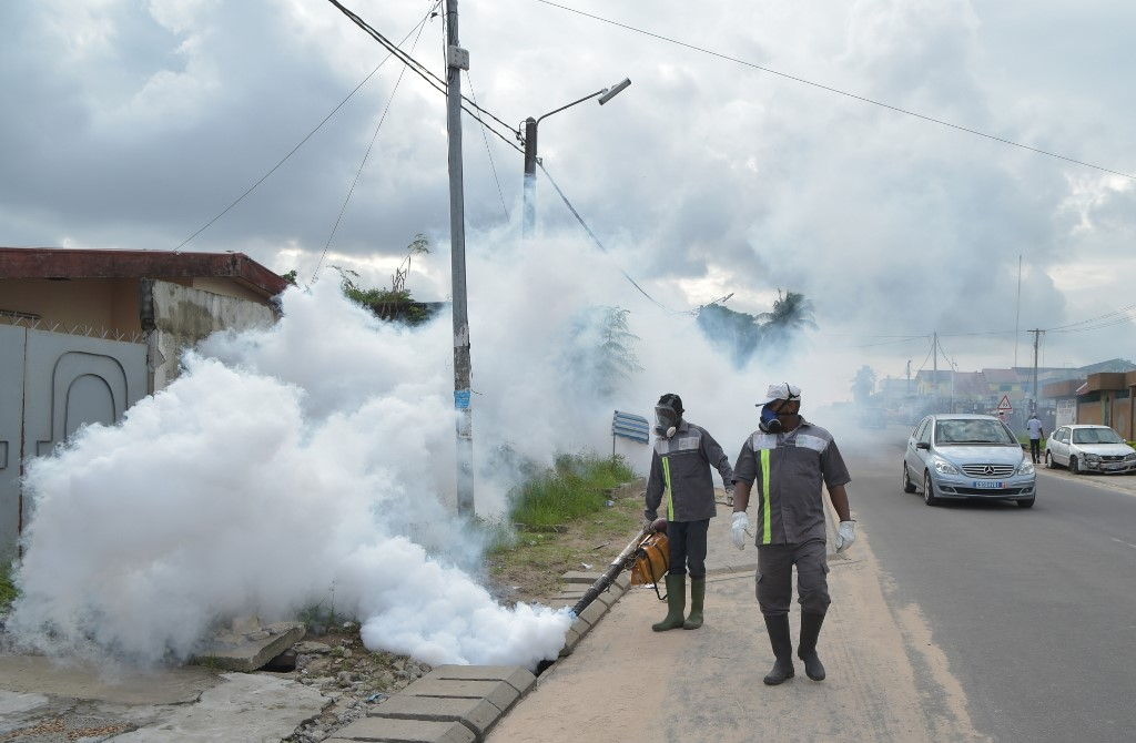 Health workers fumigate an area to prevent mosquitos from breeding, in Abidjan, as part of a campaign against the mosquito borne virus dengue