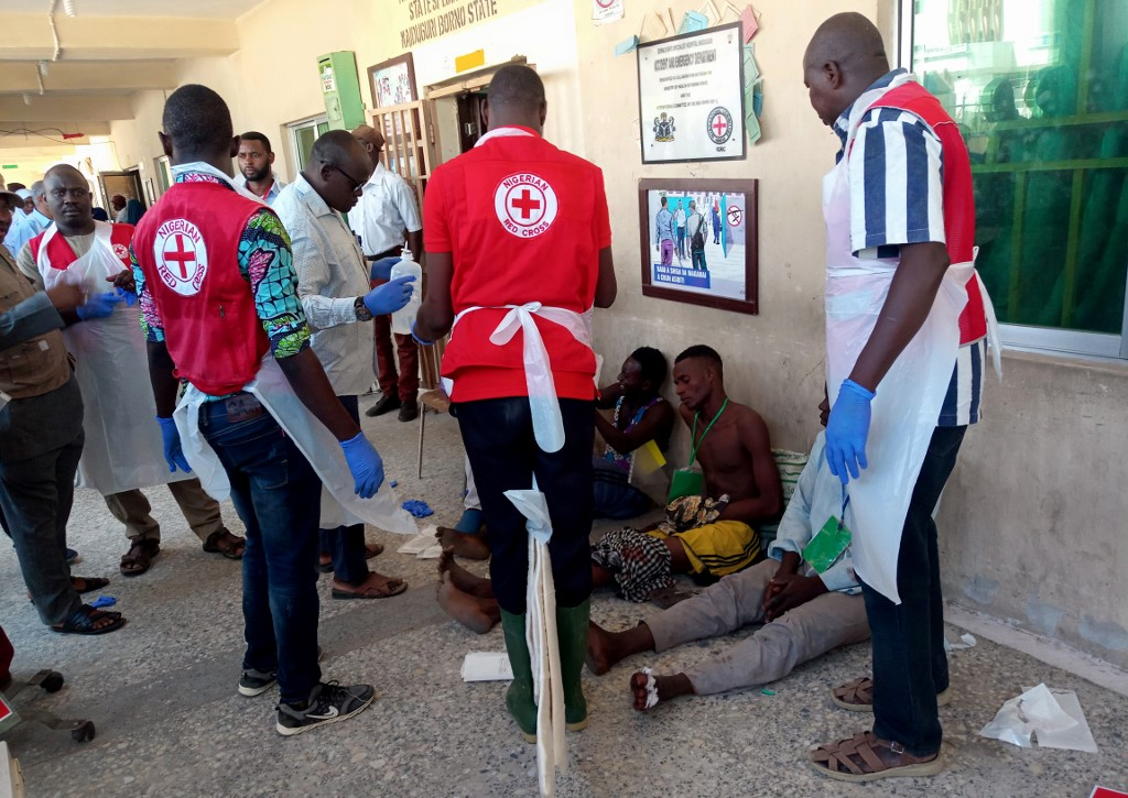 Red Cross officials attend to victims of a triple suicide bombing, in Konduga, 38 kilometres