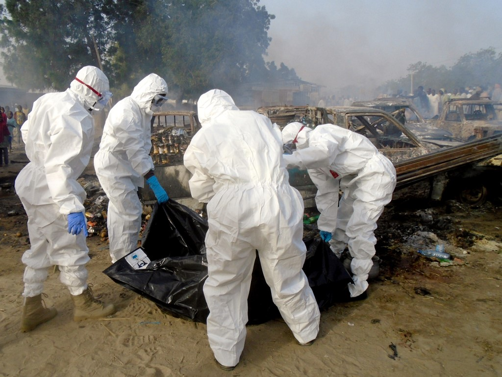 Forensics cover a dead body and clear the scene of a blast in Maiduguri