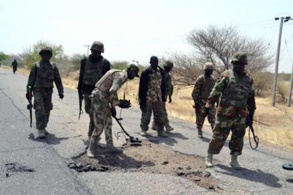 Nigerian troops clearing land mines as they advance to prevent mine explosion