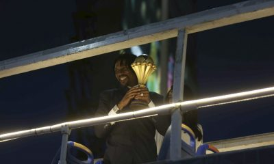 Retired Cameroonian footballer Rigobert Song holds the Africa Cup of Nations (AFCON) trophy on top of an open top bus