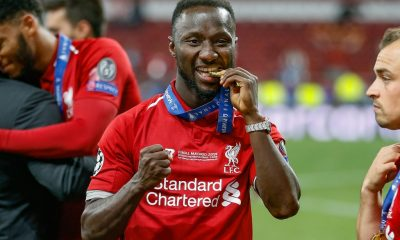 Liverpool midfielder Naby Keita, who makes the AFCON 2018 squad for Guinea bites his Winner's Medal