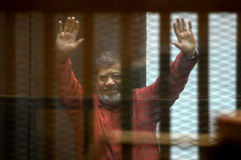 Ousted Egyptian President Mohamed Morsi greeting press members as he stands behind the bars. Morsi's Death has been reported
