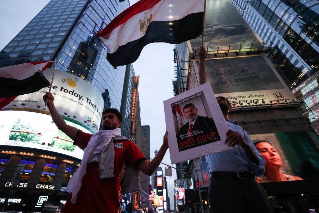 People wave flags of Egypt during a protest against the military government in Egypt after Egypt's first popularly elected president Mohamed Morsi, who reportedly died from a heart attack on Monday at a court session