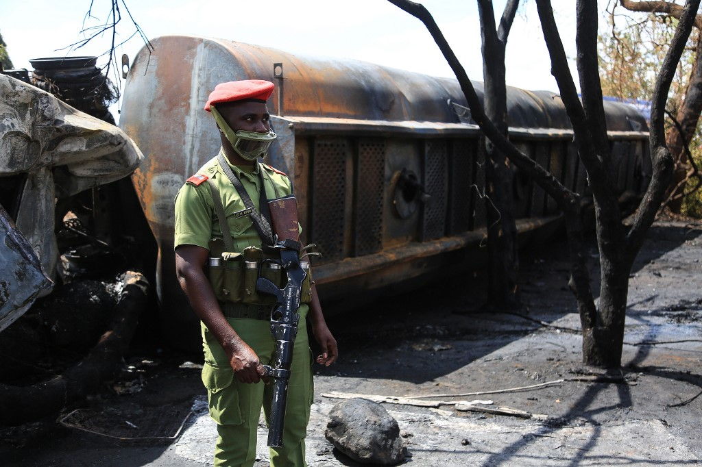 A Tanzanian security officer controls the area where the carcass of a burnt out fuel tanker is seen