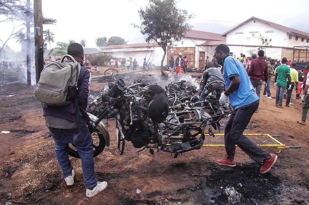 Two men carry the remains of a burnt out motorbike after a fuel tanker exploded in Tanzania
