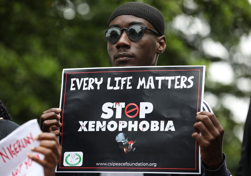 emonstrator holds a sign during a protest against xenophobia as Nigerians get free flights home