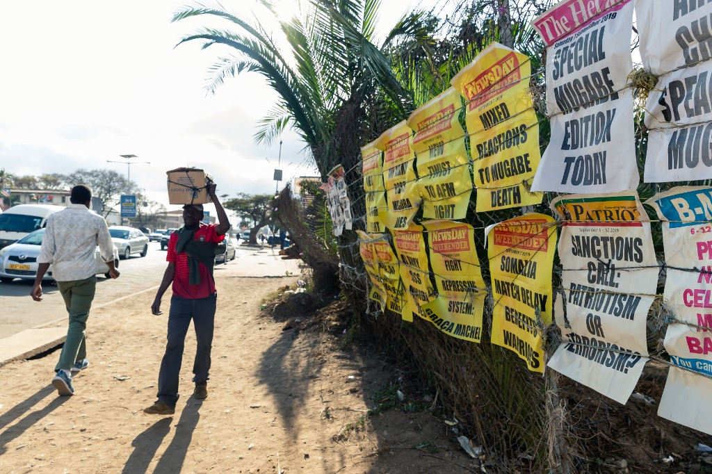 Pedestrians walk past signs of the various daily newspapers mourning following the death of former Zimbabwe president Robert Mugabe