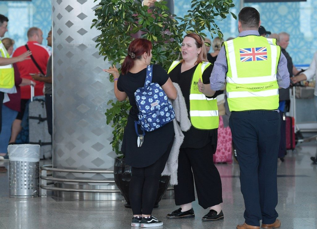 A British government official speaks to tourists, flying with Thomas Cook, as they queue at the Enfidha International airport on September 23, 2019, on the outskirts of Sousse south of the capital Tunis