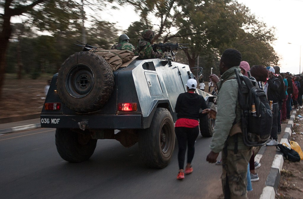 Protesters watch a Malawi Defence Force armoured vehicle in Malawi where a police officer was killed
