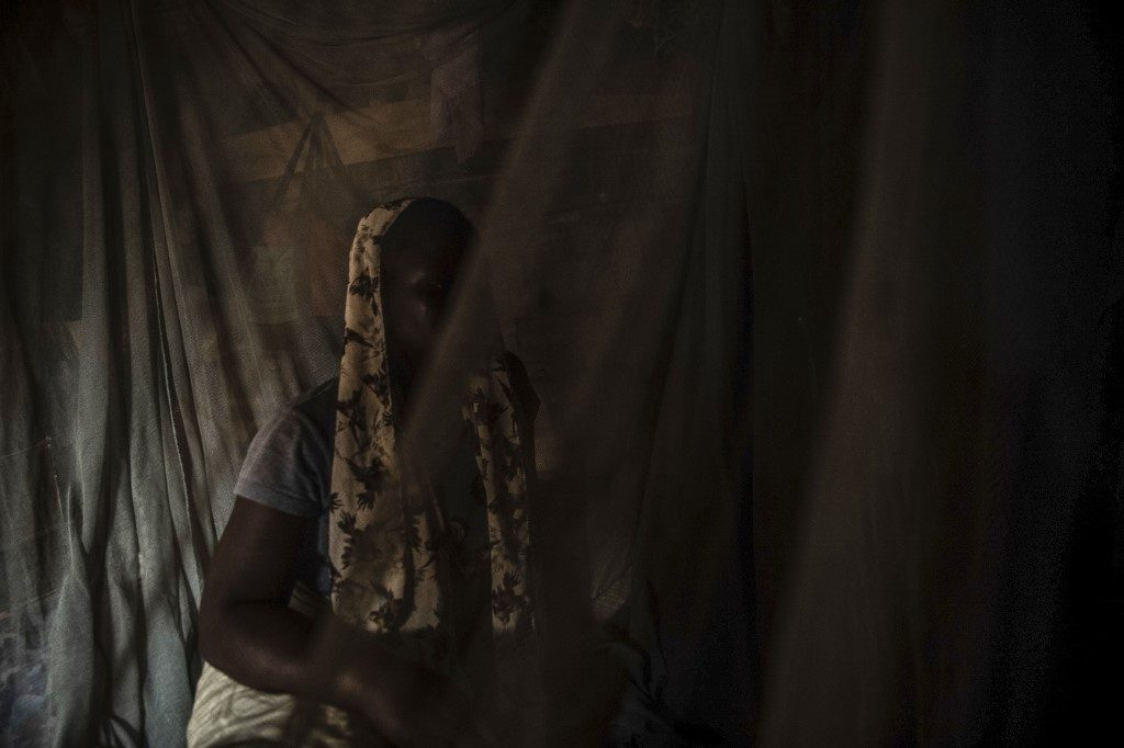 An internally displaced person (IDP) from Borno State, who escaped the Boko Haram insurgency to join the International Christian Center (ICC), a camp set up by Pastor Solomon Folorunsho in Benin City, where children and staff have complained of hunger and abuse, sits behind curtains in Abuja on July 5, 2019