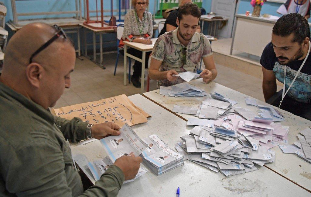 Tunisian electoral officials count the ballots