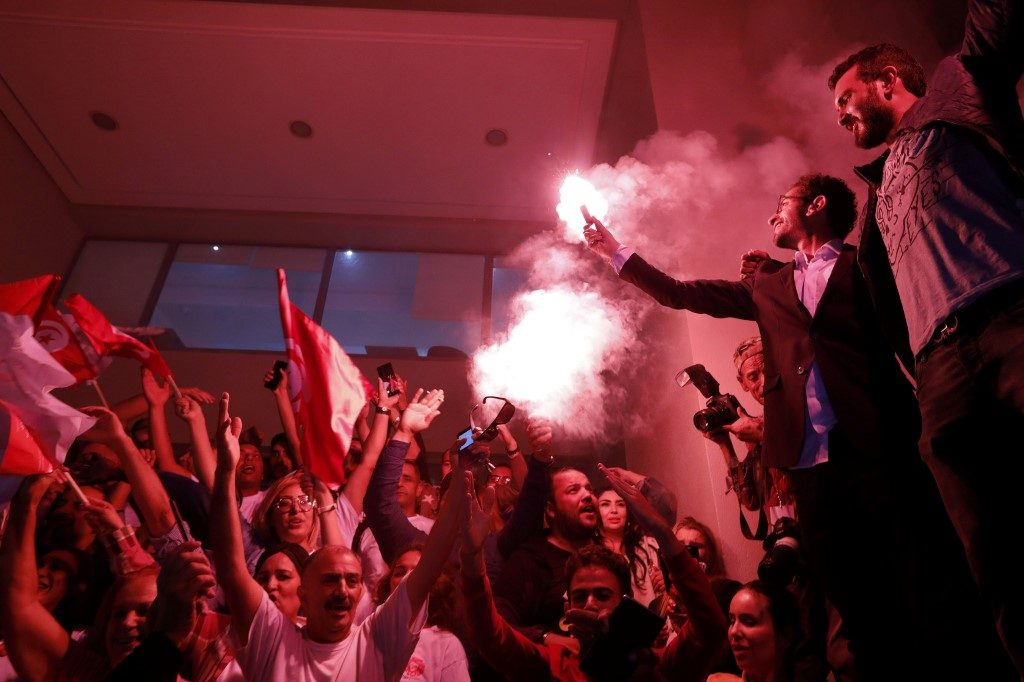 Supporters of Tunisian presidential candidate and media magnate Nabil Karoui celebrates after he was released from Mornaguia prison