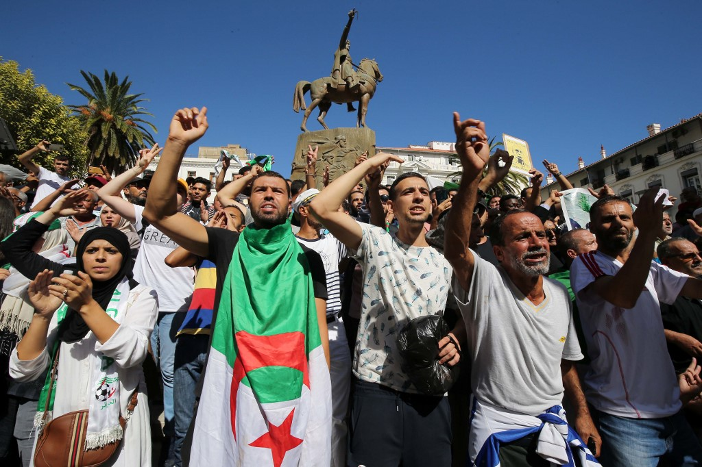 Algerian protesters carrying national flags chant slogans during a students' demonstration