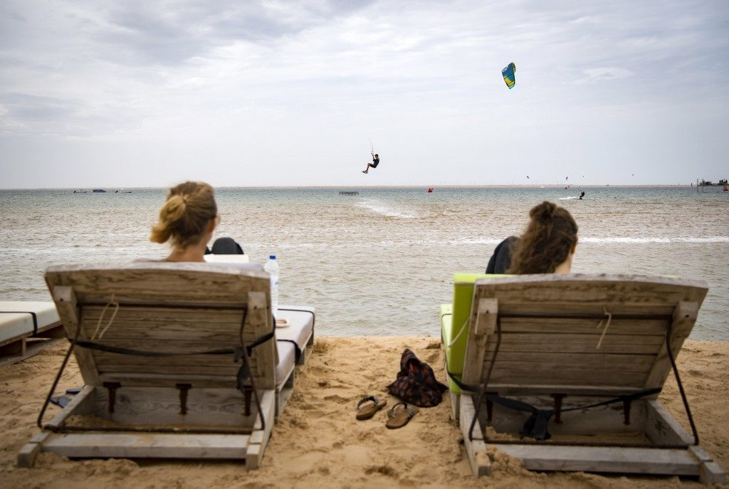 Tourists watch kitesurfers at Dakhla beach in Morocco-administered Western Sahara