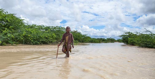A young boy navigates a flooded road in Somalia